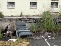 Environmental blight: old furniture discarded in an old parking lot outside a disused building