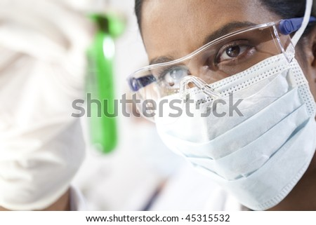 Environmental concept shot of a female Asian medical or scientific researcher or doctor looking at a test tube of a green solution in a laboratory.