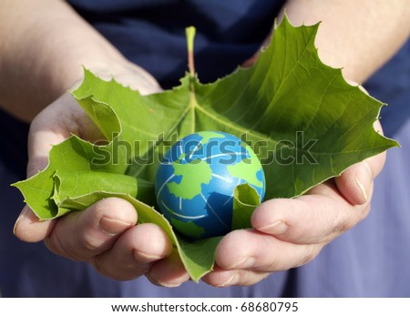 Environmental conservation Concept: Hands of an environmentally minded Person holding a leaf for protection of small eco friendly blue and green globe of the earth.
