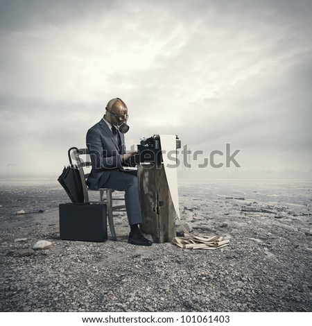 environmental disaster: businessman  wearing a gas mask, write with an old typewriter
