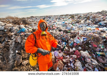 Environmental engineer standing on the landfill in front of the municipal waste measuring pollution