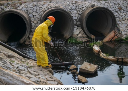 Environmental factory workers are checking oil stains from the factory effluent system. Pollution industry . stock photo