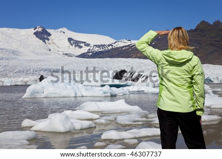 Environmental picture of woman hiker dressed in green jacket looking at the effects of global warming climate change on a melting glacier with icebergs floating into a glacial pool.
