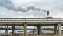 Environmental pollution. Environmental problem. Highway overpass, under the viaduct. View of the powerful concrete pillars and Smoking pipes of a large enterprise. The concept of urbanization.