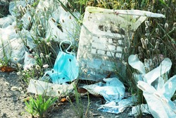 Environmental pollution with personal protective equipment against the virus and plastic bags. Used face mask, disposable gloves on the ground among grass and other rubbish outdoors in the evening