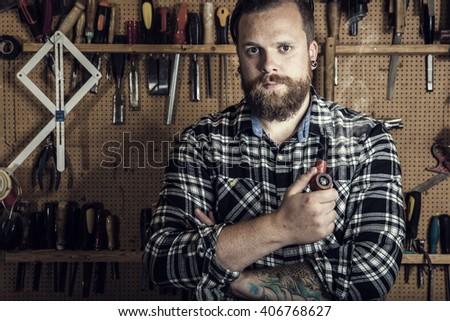 Environmental portrait of a man smoking pipe in wood workshop