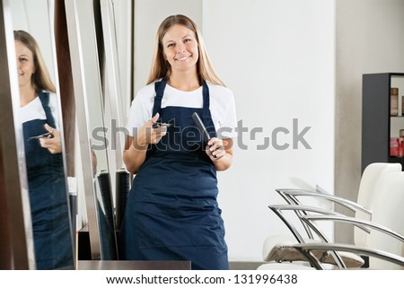 Environmental Portrait of beautiful female hairdresser holding comb and scissors at salon
