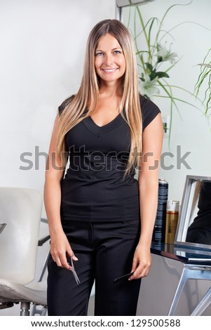 Environmental portrait of happy mid adult female hairdresser standing at salon