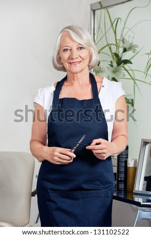 Environmental portrait of senior female hairdresser holding scissors and comb while standing at salon