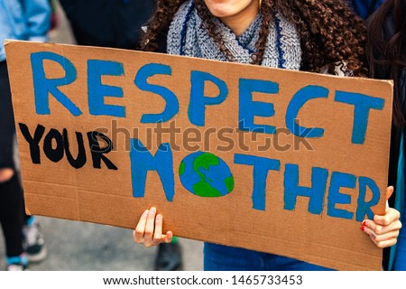 Environmentalist sign at climate rally. A close up shot of a homemade cardboard poster, saying respect our mother, held by a woman during a street protest for environmental issues. Stock foto ©
