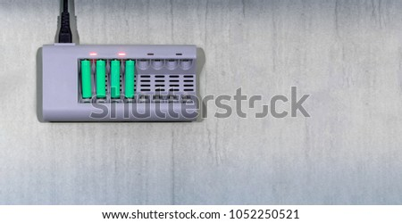 Environmentally Friendly Rechargable Batteries on a Charger Foto stock ©