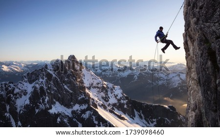 Epic Adventurous Extreme Sport Composite of Rock Climbing Man Rappelling from a Cliff. Mountain Landscape Background from British Columbia, Canada. Concept: Explore, Hike, Adventure, Lifestyle Photo stock ©