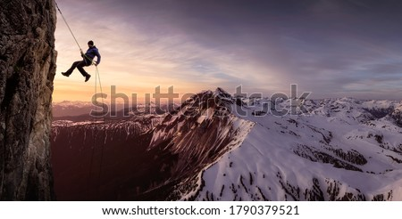 Epic Adventurous Extreme Sport Composite of Rock Climbing Man Rappelling from a Cliff. Mountain Landscape Background from British Columbia, Canada.