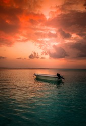 Epic beach sunset view with boat, dramatic Maldives Island scenery orange color cloudy sky and green turquoise color sea, Epic beach images