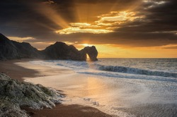Epic colorful sunrise over ocean landscape scene with cliffs and beautiful cloud formations