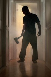 Epic concept with man in silhouette holding axe inside a smoking house at night