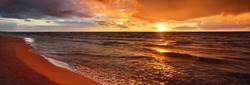 Epic dark sunset sky above the sea shore after the storm. Dramatic glowing colorful red clouds, natural texture, background. Fickle weather, climate change, ecology. Panoramic view