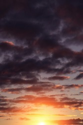 Epic dramatic sunset, sunrise on storm sky with dark clouds, orange yellow sun and sunlight