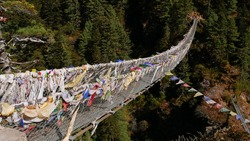 Epic Hillary Suspension Bridge on the way up to Namche Bazar, Himalayas, Nepal on Everest Base Camp Trek spanning a canyon (depth ca. 70 m) with colorful Buddhist prayer flags waving in the wind.