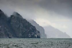 Epic panorama of the Bering Sea coastline. View of the huge rocky capes. Nature of the far North of Russia and the Arctic. Eastern coast of Chukotka, Russian far East. Gloomy cloudy autumn weather.