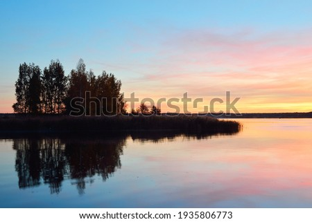 Epic red and golden clouds above the forest lake at sunrise. Dramatic cloudscape. Symmetry reflections on the water, natural mirror. Idyllic rural scene. Gauja national park, Sigulda, Latvia