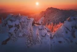 Epic red sunset over the rocks and stones of Ural mountains covered with snowy pines. Taganay national park, Russia