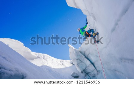 Epic shot of an ice climber climbing on a wall of ice. Mountaineer and climber on an adventure extreme ascent with ice axe and crampons. Alpine extreme climbing on a serac or creavasse. #1211546956