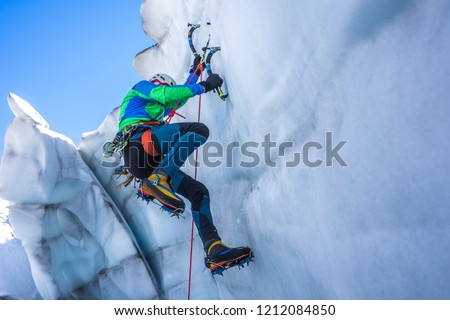 Epic shot of an ice climber climbing on a wall of ice. Mountaineer and climber on an adventure extreme ascent with ice axe and crampons. Alpine extreme climbing on a serac or crevasse.