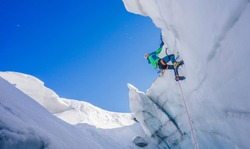 Epic shot of an ice climber climbing on a wall of ice. Mountaineer, climber or alpinist on an adventure extreme ascent with ice axe and crampons. Alpine extreme climbing on a serac or creavasse.
