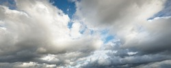 Epic storm cloudscape. White ornamental sunset cumulus clouds. Soft sunlight, sun rays. Clear blue sky. Natural pattern, texture, background, wallpaper, 3D, graphic resources, design, copy space