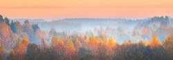 Epic sunrise and fog above the hills, field and forest. Colorful autumn landscape. Idyllic rural scene. Dramatic sky with yellow, orange, pink and red clouds. Pure morning light