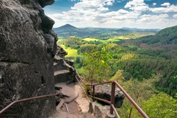 Epic view from Rock of Maria, or Mariina skala, or Marienfels into beautiful landscape of Bohemian Switzerland on a sunny summer day. View from the top of the rock into vast, picturesque landscape.