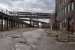 Epic wide angle shot of crossing elevated train tracks and vintage red brick abandoned factory in a depressed industrial urban blue collar area of St. Louis Missouri with cloudy sky