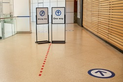 Epidemic protection measures in shops or shopping malls - two way direction signs. Social Distance Safety Indoor Shopping.  Life after pandemic. Secure marking of lines on floor for waiting in store.