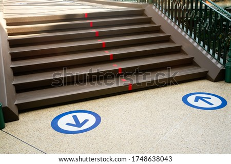 Epidemic protection measures in shops, shopping malls or centres floor blue circle stickers with arrow . Social Distance Shopping. Life after virus. Secure marking of lines on floor for directions,