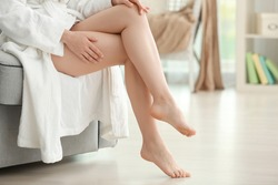 Epilation concept. Legs of beautiful young woman sitting on sofa