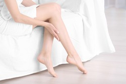Epilation concept. Young woman sitting on sofa, closeup view of female legs