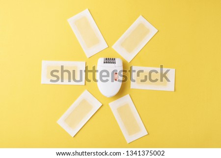 Epilator and wax strips on yellow background. Set for depilation, bodycare concept #1341375002