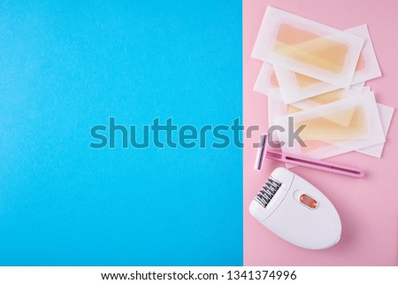Epilator, razor for shaving and wax strips on blue and pink background with copy space. Set for depilation, bodycare concept #1341374996
