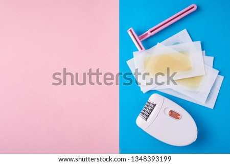 Epilator, razor for shaving and wax strips on blue and pink background with copy space. Set for depilation, bodycare concept #1348393199