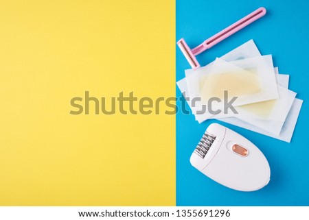 Epilator, razor for shaving and wax strips on blue and yellow background with copy space. Set for depilation, bodycare concept #1355691296