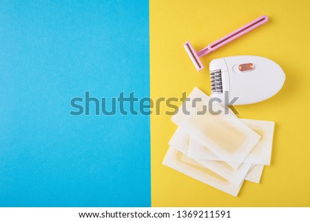 Epilator, razor for shaving and wax strips on blue and yellow background with copy space. Set for depilation, bodycare concept #1369211591