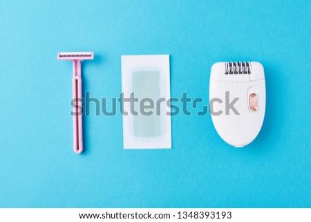 Epilator, razor for shaving and wax strips on blue background. Set for depilation, bodycare concept #1348393193