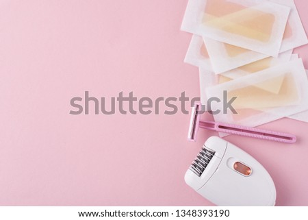 Epilator, razor for shaving and wax strips on pink background with copy space. Set for depilation, bodycare concept #1348393190
