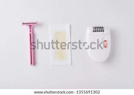 Epilator, razor for shaving and wax strips on white background. Set for depilation, bodycare concept #1355691302