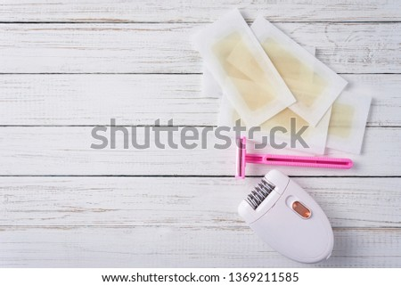 Epilator, razor for shaving and wax strips on white wooden background with copy space. Set for depilation, bodycare concept #1369211585