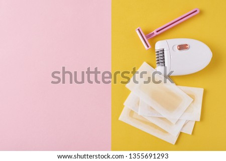 Epilator, razor for shaving and wax strips on yellow and pink background with copy space. Set for depilation, bodycare concept #1355691293
