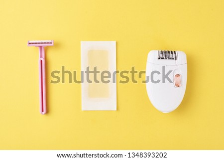 Epilator, razor for shaving and wax strips on yellow background. Set for depilation, bodycare concept #1348393202