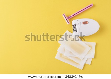 Epilator, razor for shaving and wax strips on yellow background with copy space. Set for depilation, bodycare concept #1348393196