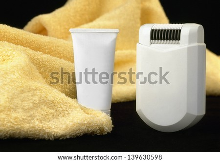epilator with a bottle of lotion and a towel
